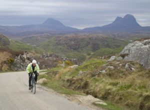 Me struggling up one of the many steep roads in NW Scotland. Here, the kinetic energy of me and my bike is much less than the kinetic energy of a drifting tectonic plate. In fact the speed of me and my bike is probably less than that of a drifting tectonic plate.